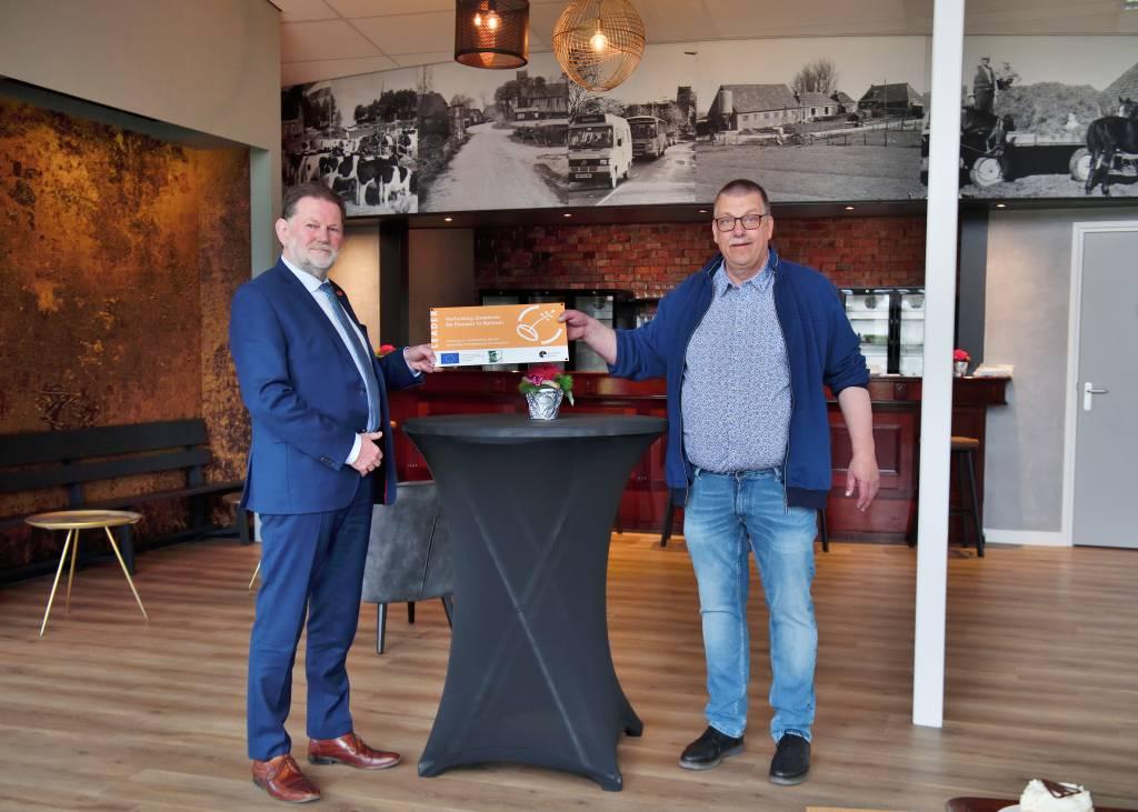 Oane Sierksma fan De Fjouwer krijt it Leader-buordsje foar doarpshûs  De Fjouwer yn Reitsum út hannen fan deputearre Klaas Fokkinga.