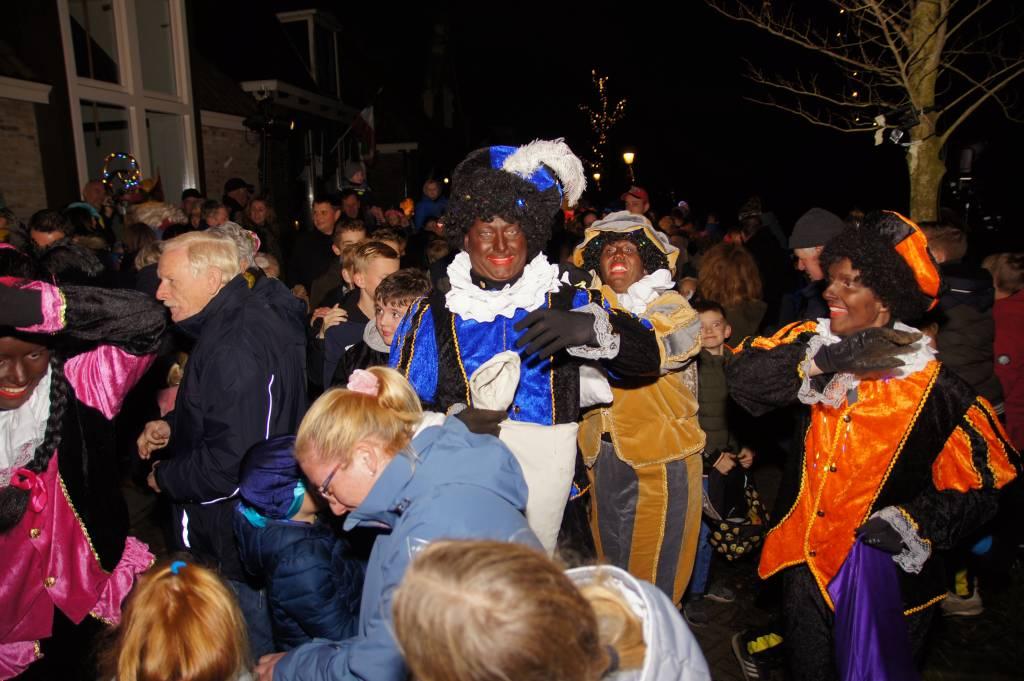 Terwijl Sinterklaas (links) zich al handenschuddend een weg door de menigte baant, verrassen de hossende en dansende zwarte Pieten het publiek met pepernoten (foto Bertus Dijkstra)
